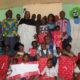 Le ministre Jean Claude Kouassi assis au milieu des enfants après leur avoir remis quelques cadeaux